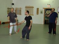 In the Kwoon, Introduction to T'ai Chi Straight Sword (March 2007): Demonstrating Pushing Sword with Si-Hing Joel Valerio and Water Tiger student Ed Merchant watching, McElroy Laoshi (L) shares the various Post-It® notes of the exercise – step through the mat, move with the whole, flow, relax, breathe, maintain edge-to-edge contact, eyes up, etc.