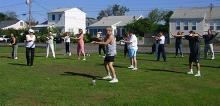T'ai Chi in the Park (September 1, 2007): Nancy Fiano (second from the Left in white), Dojo of the Dancing Dragon in Lindenhurst, leads an exercise in coiling, spiraling, and body awareness.