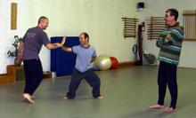 In the Kwoon, Perspectives on T'ai Chi Push Hands (November 2007): With smiles all around, Laoshi Laurince McElroy (L) demonstrates Water Tiger School's Single-Hand Moving Push Hands (Sticky Hands) exercise with Si-Hing Joel Valerio while Bob LaMantia observes.