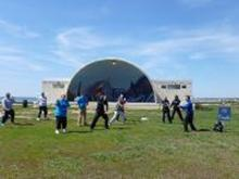 "World T'ai Chi & Qigong Day — Patchogue (April 27, 2013): Framed by the beautiful Shorefront Park Band Shell, Bill Donnelly (R), Green Cloud Kung Fu of Holbrook, helps people ""thread the nine-holed pearl"" with Silk Reeling (Chan Si) exercises."