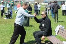 "World T'ai Chi & Qigong Day — Patchogue (May 3, 2014): Using a bench to demonstrate the importance of relaxed structure, Elan Abneri (R), a senior student of Sifu Tyrone ""Wei"" Wicksman at Zhang Style Tai Chi Chuan in Centereach, leads his workshop focusing on an in-depth exploration of hip alignment with attention on the rear leg. Photo by Joe Cavaliere, taichi-daily.com."